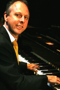 Phil Carrol, piano player, wearing a suit with a yellow tie